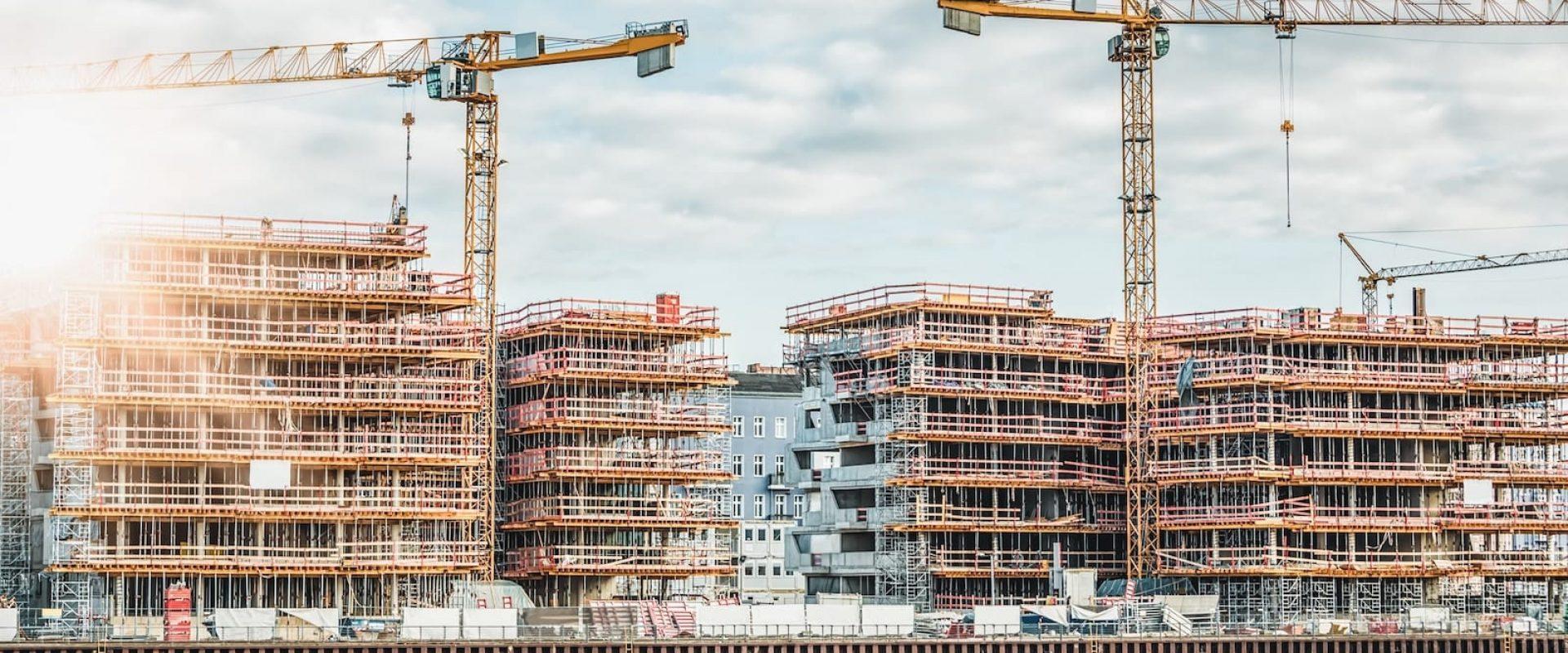 Viser høye bygg som er under konstruksjon. Byggene er dekket av stillas og det er kraner på byggeplassen.