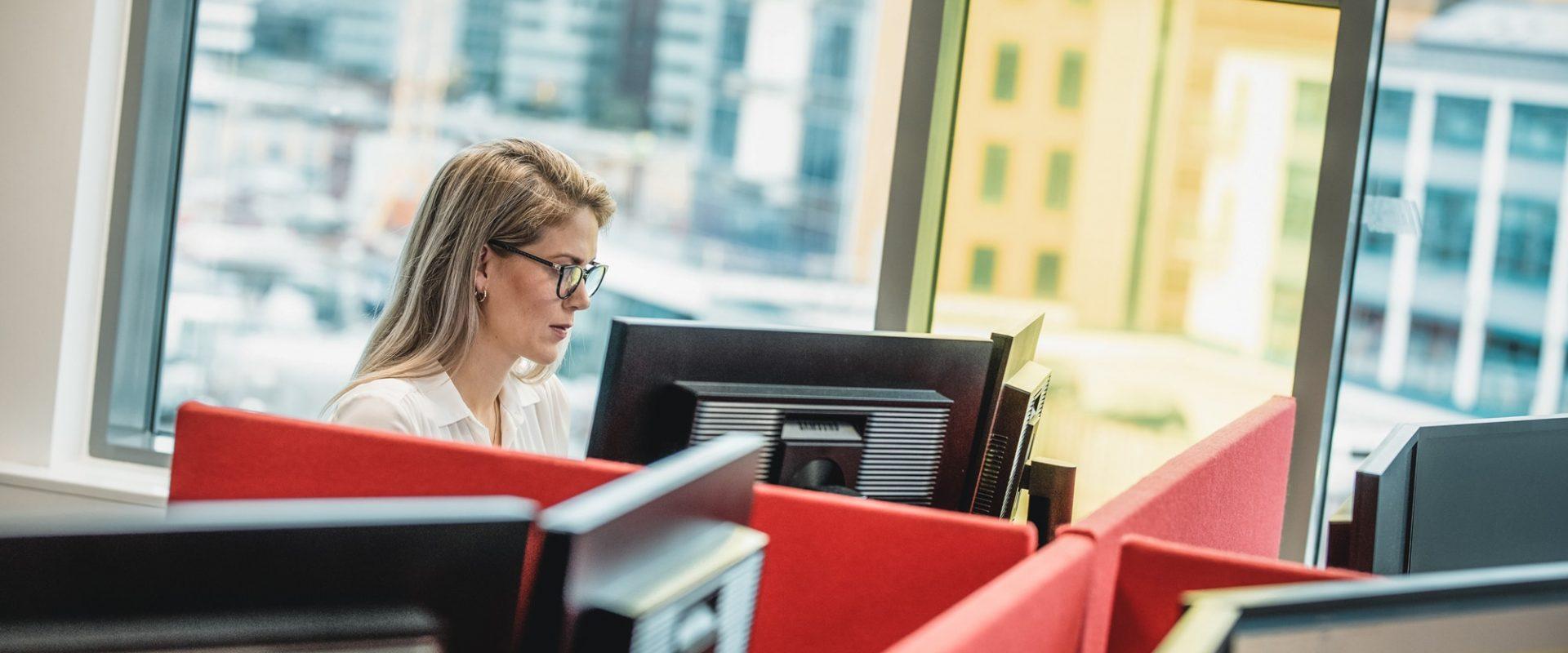 Kvinne foran datamaskin i kontorlandskap hos Inventura.