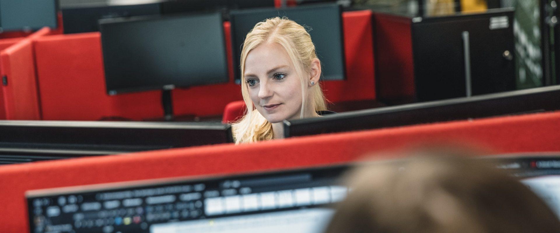kvinnelig ansatt som jobber foran datamaskin i kontorlandskap hos Inventura.