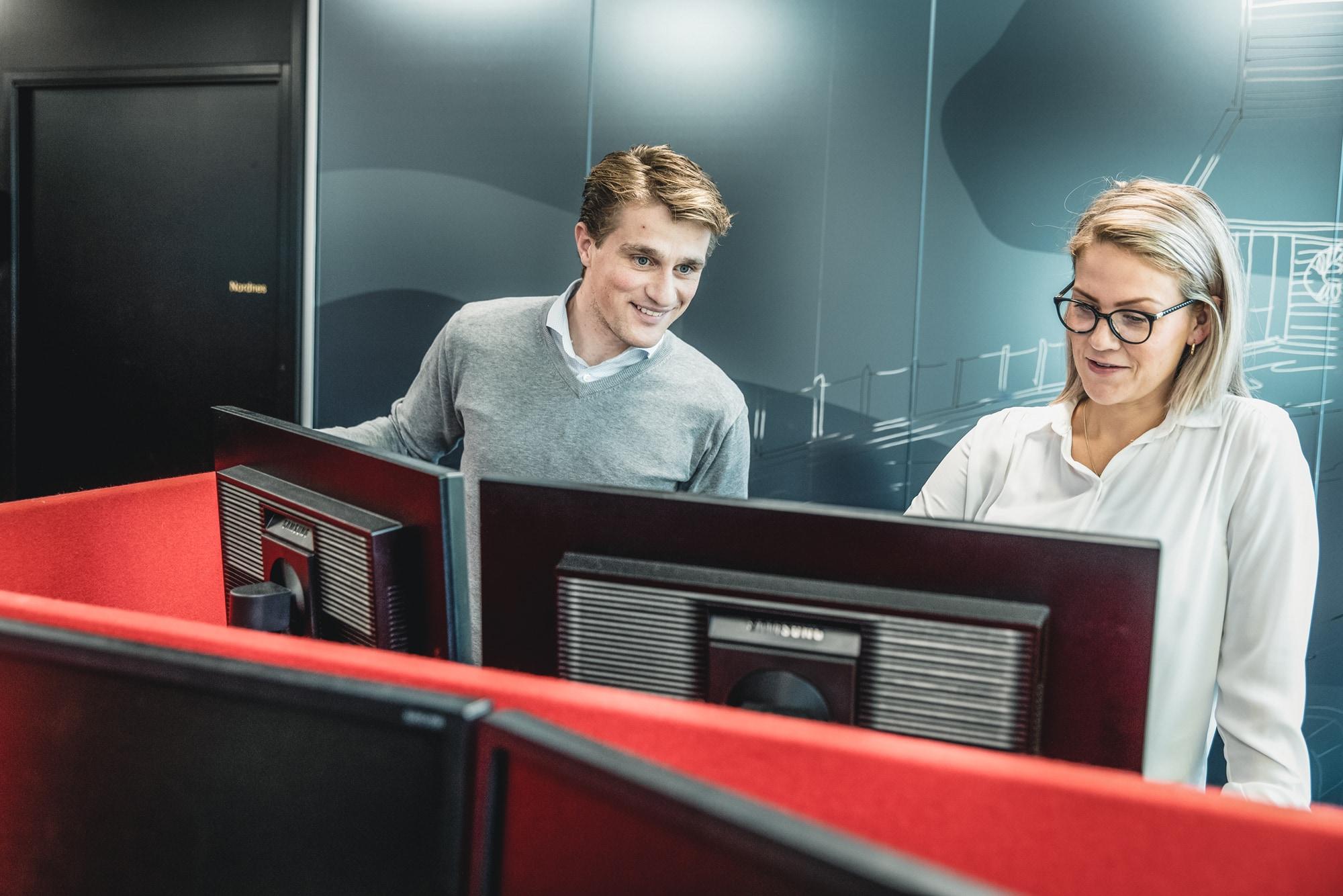 Mannlig og kvinnelig kollega ser på datamaskiner i kontorlandskap hos Inventura. Selskapet kan blant annet bistå med å etablere kategoristyring.