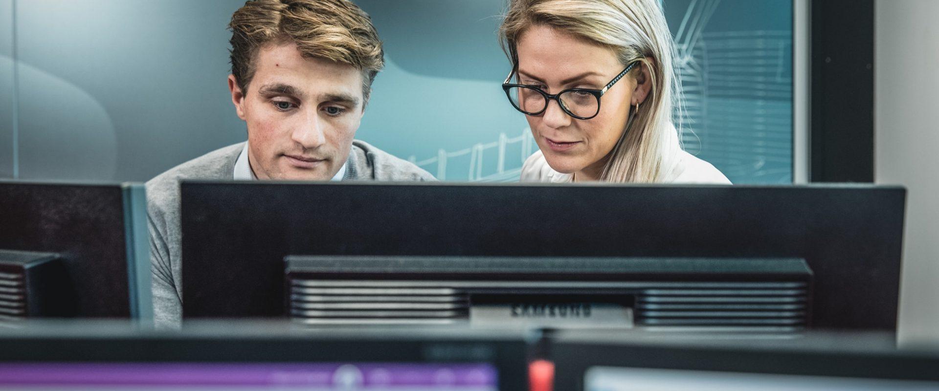 To kollegaer som ser på en PC skjerm hvor de kan jobbe med kategoristyring. Spendency er et godt digitalt verktøy for dette.