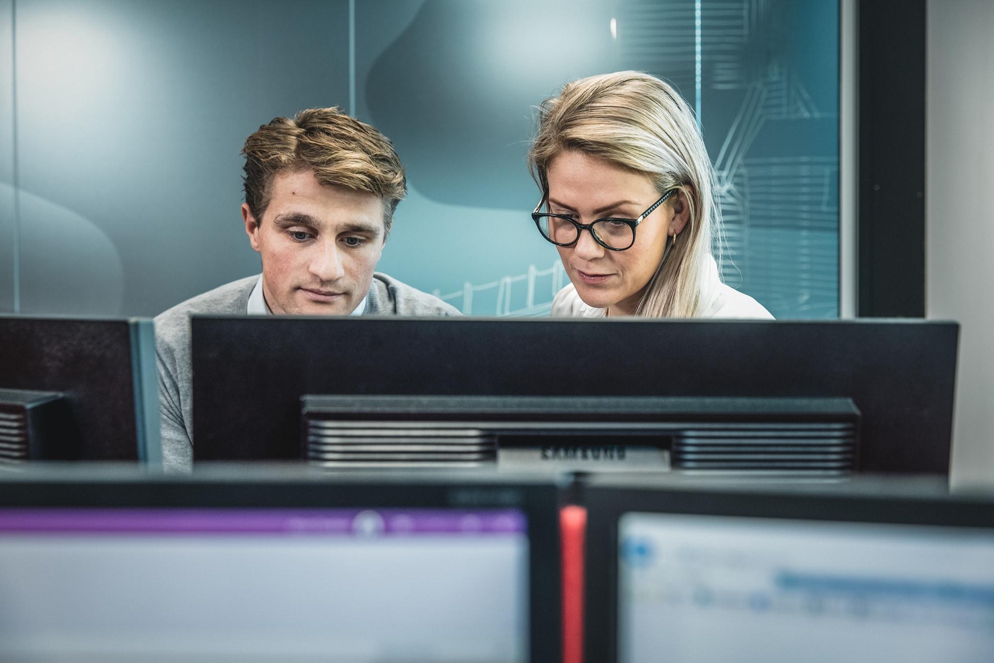 En mann og en dame jobber konsentrert foran pc-skjermer i kontorlandskap hos Inventura.