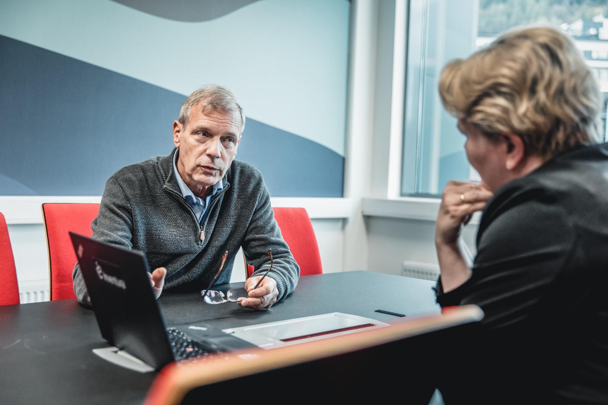 Mannlig og kvinnelig kollega i dialog på møterom i Inventuras kontorlokaler. Selskapet tilbyr blant annet tjenester om implementering av innkjøpsavtaler.