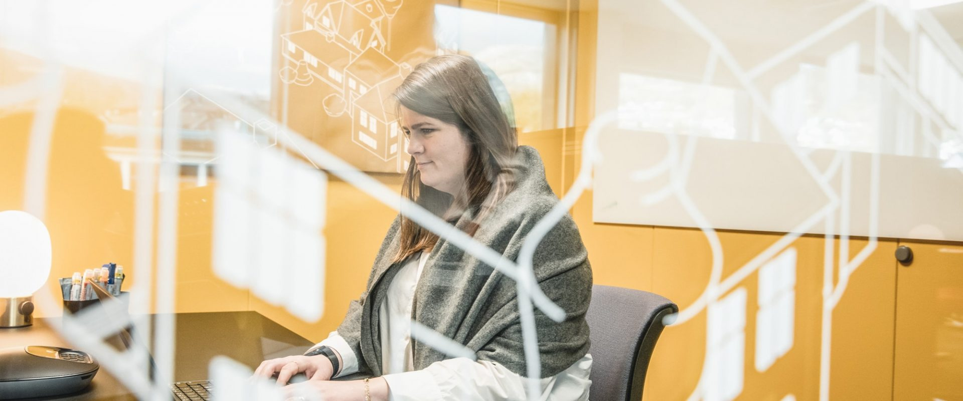 Kvinnelig kollega som jobber foran pc i Inventuras møterom. Selskapet bistår blant annet med verdikjedeutvikling