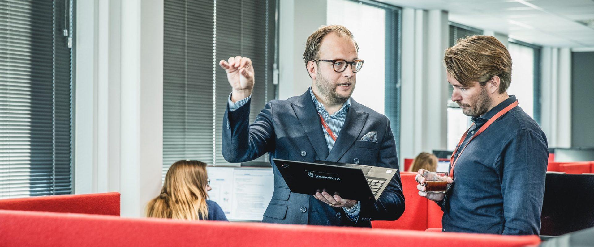 To kollegaer som diskuterer innkjøp over en laptop.