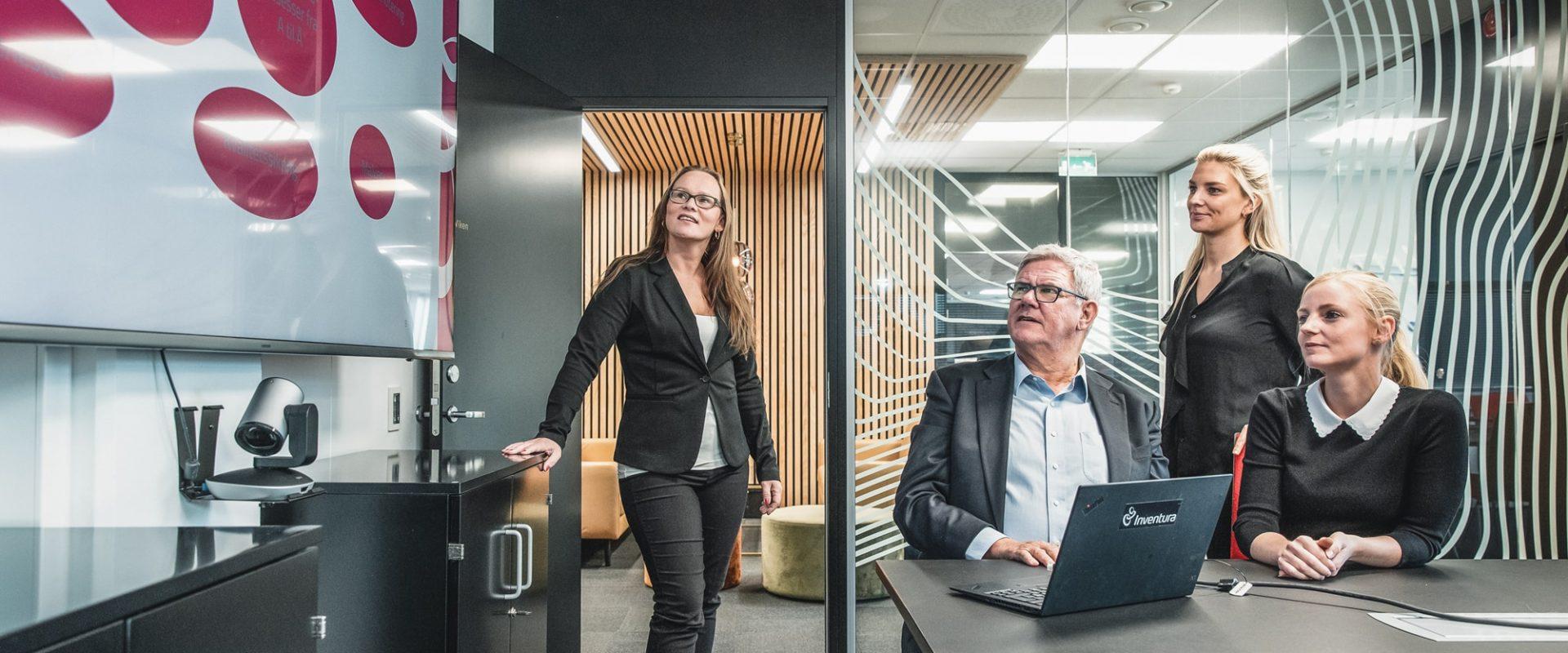 Fire kollegaer står inne på et møterom og ser på en tavle med leverandørporteføljen. Leverandøranalyse er viktig for å ha en god leverandørportefølge.