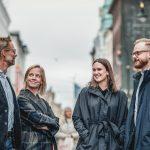 fire kollegaer hos Inventura som står nede på Karl Johan og smiler