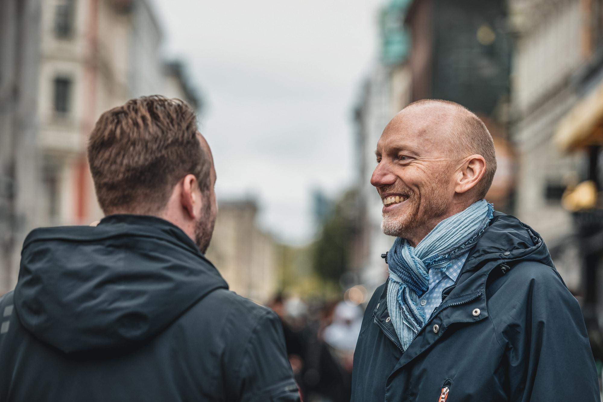 To kollegaer som står ute på karl johan og smiler