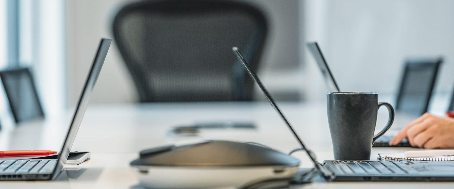 Viser et kontorbord eller arbeidsplass med flere laptoper
