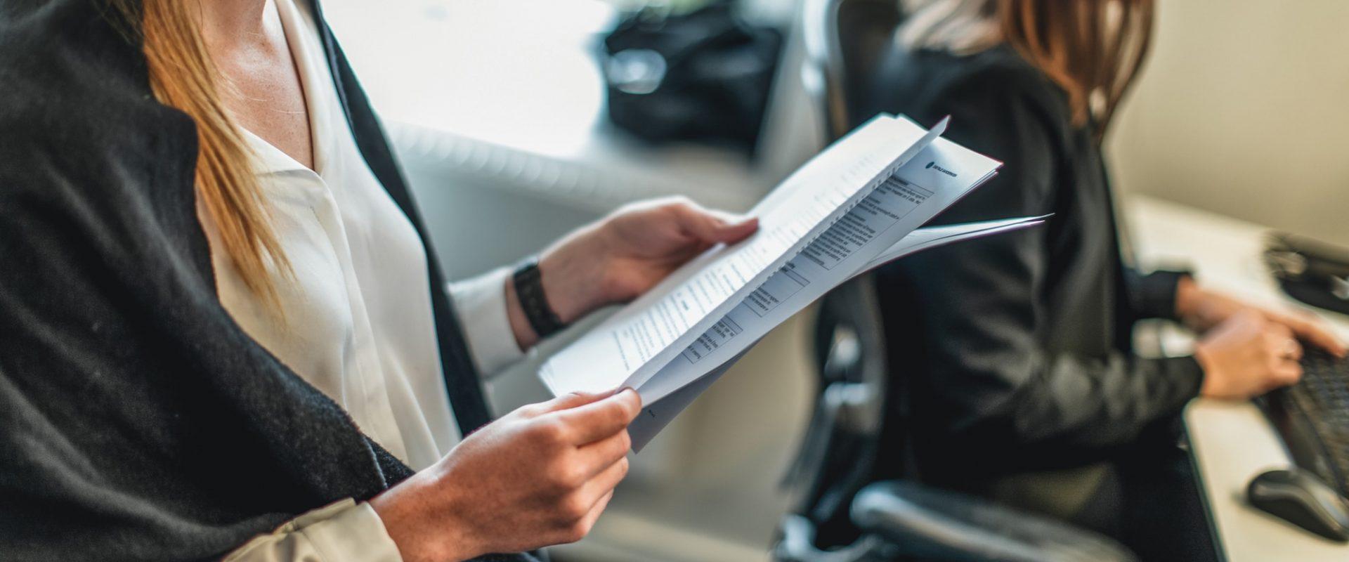 Viser en Inventuransatt som studerer et dokument. Inventura tilbyr kategoristyring som tjeneste.