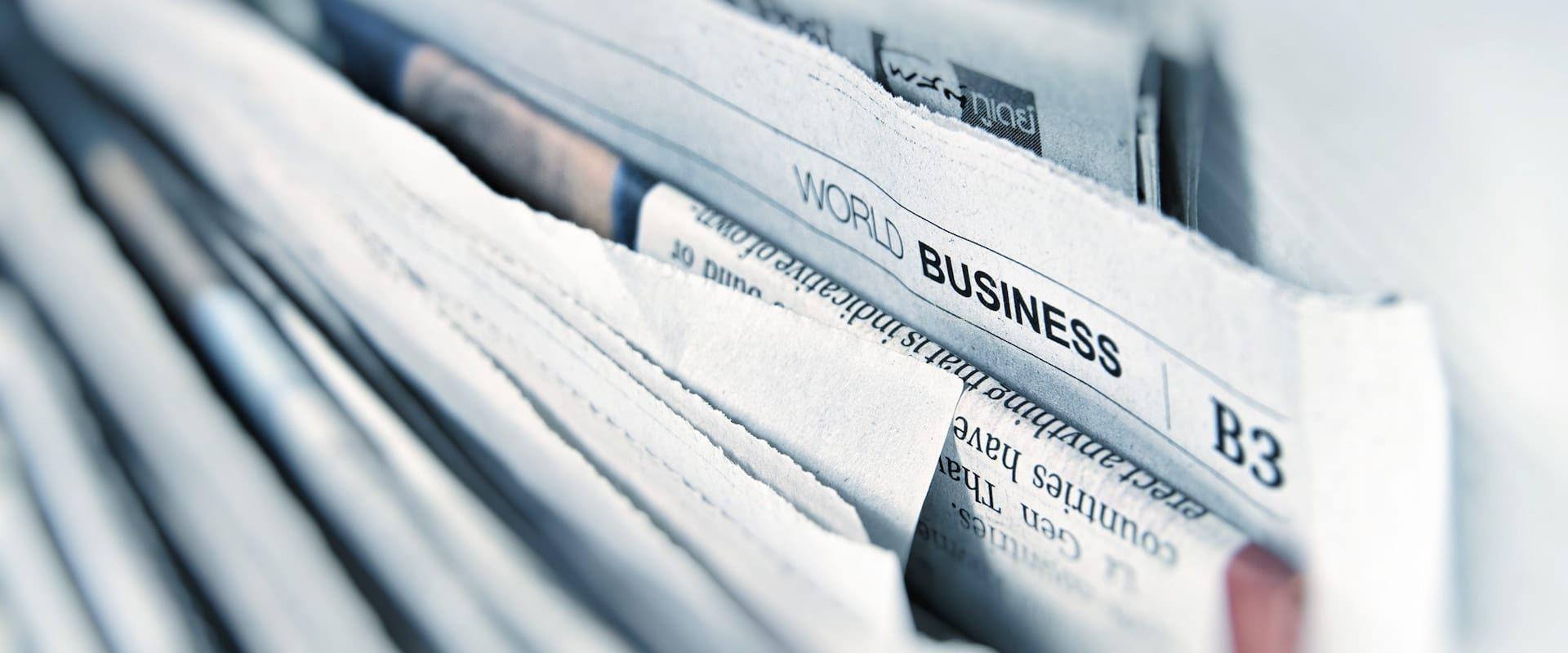 Nærbilde av mange aviser med skriften