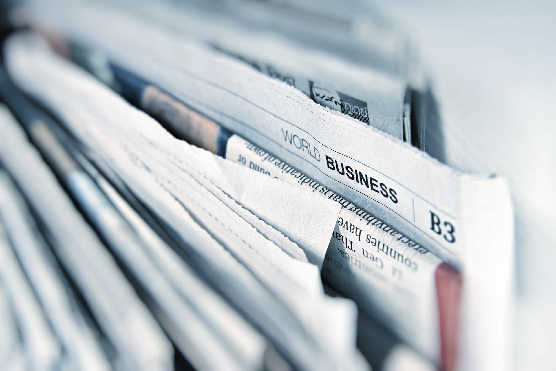 """Nærbilde av mange aviser med skriften """"world business"""" er i fokus"""