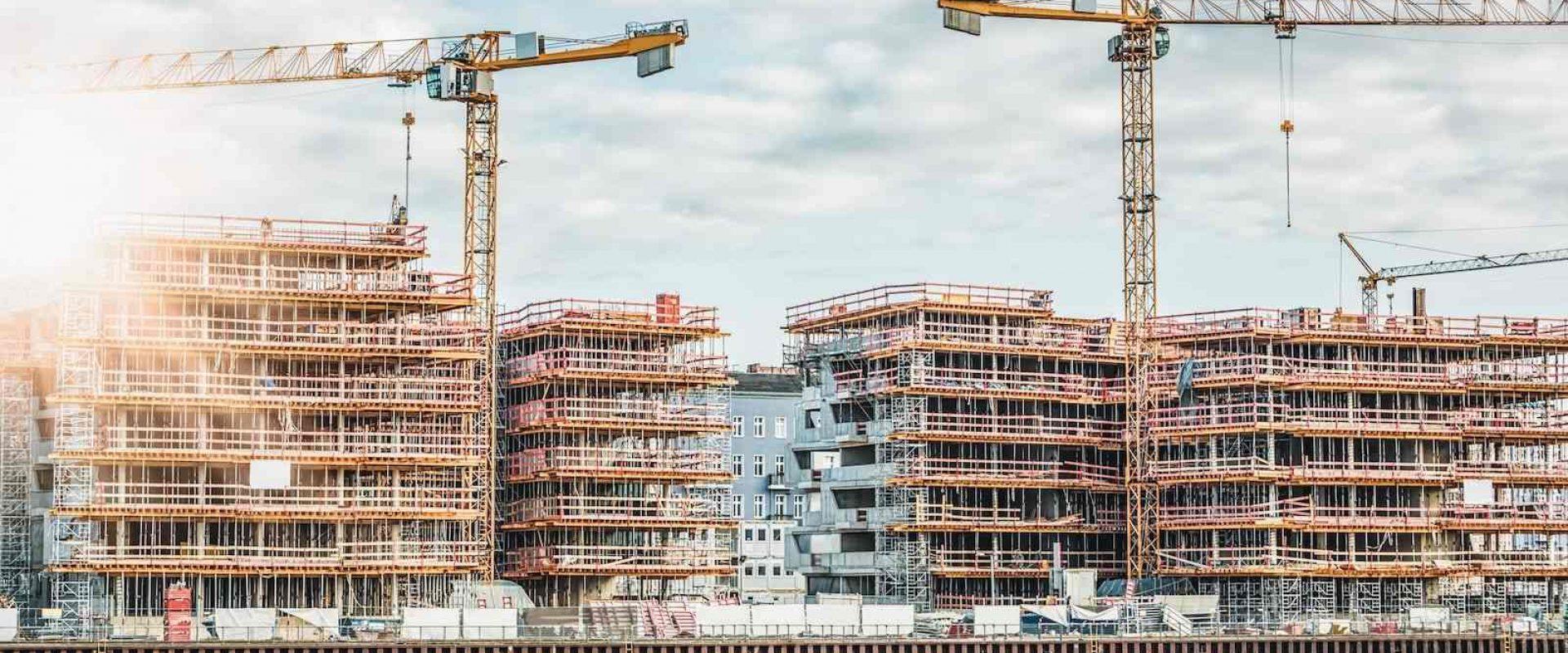 Eiendomsutvikling i byen, der store bygg er dekket av stillas og kraner på byggeplassen.