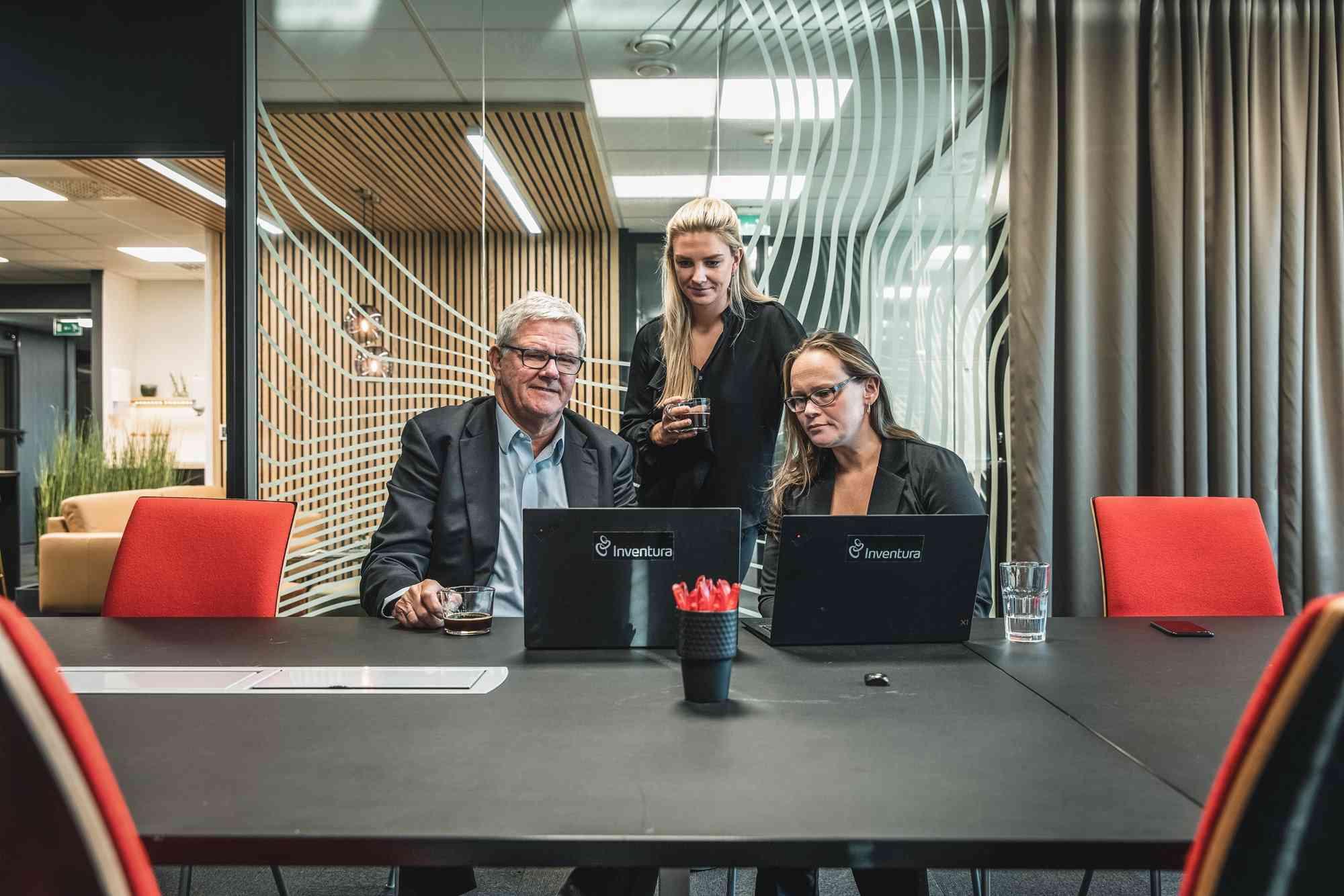 Tre kolleger i dialog i et av møterommene hos Invantura. Selskabet bistår blant annet med innkjøpsstrategi