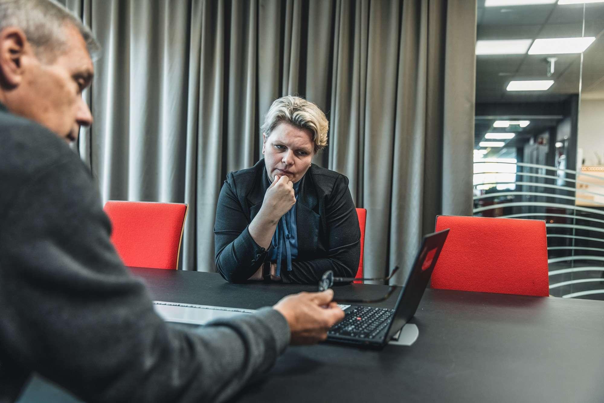 To kolleger i Inventura ser på pc-skjerm og diskuterer i møterom. Selskapet bistår blant annet med kontraktsoppfølging.