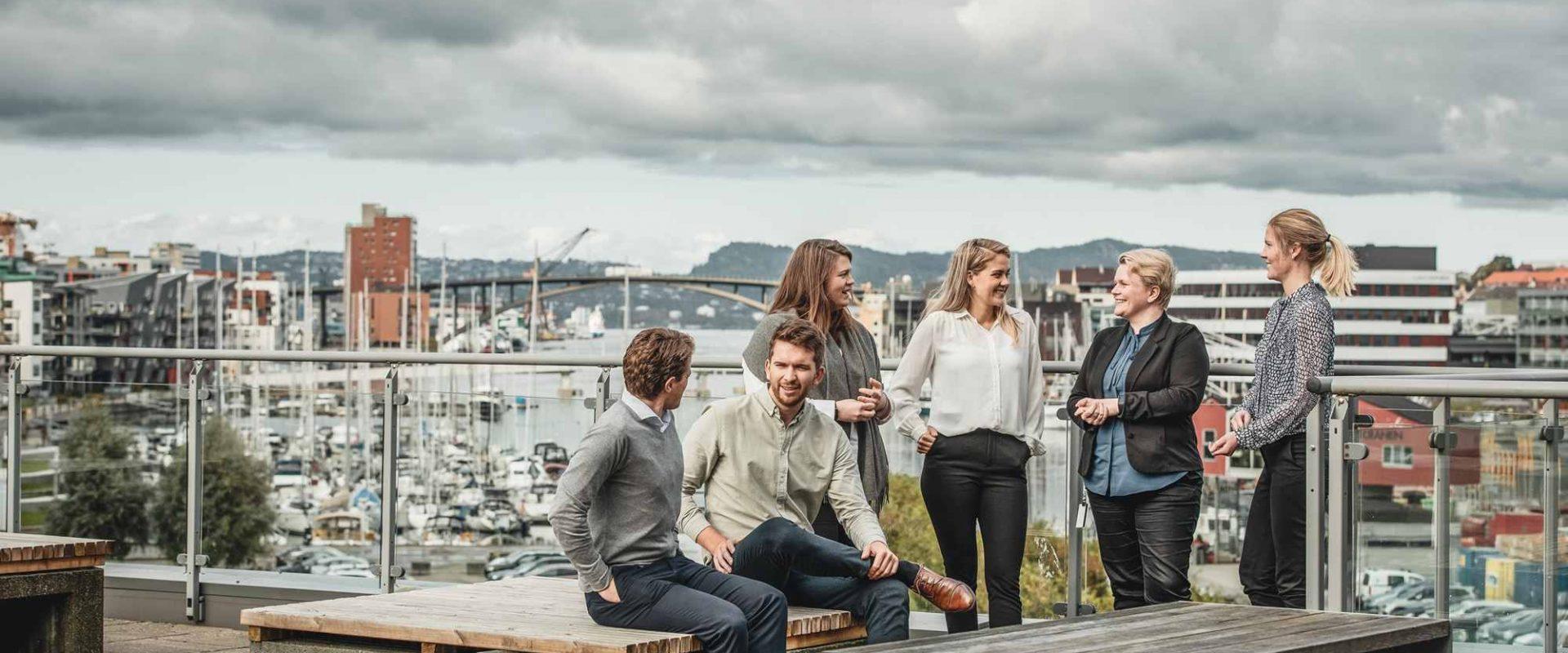 En gruppe kollegaer i Inventura snakker om samfunnsansvar på en takterrasse med utsikt utover Bergen by.